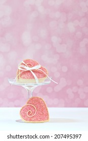 Heart shaped cookies tied with ribbon. Shot with copy copy space on pink background.