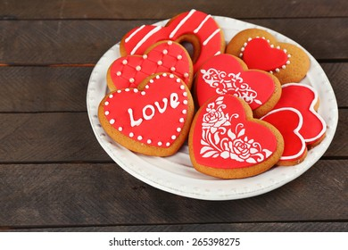 Heart shaped cookies for valentines day on plate, on wooden background
