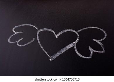 Heart shaped drawing with wings on blackboard