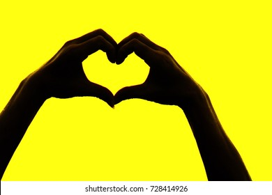 A heart shaped finger is a symbol of love, attachment, compassion and friendship. Heart-shaped silhouette on a yellow background with copy space.