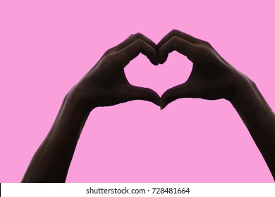 A heart shaped finger is a symbol of love, attachment, compassion and friendship. Heart-shaped silhouette on a pink background with copy space.