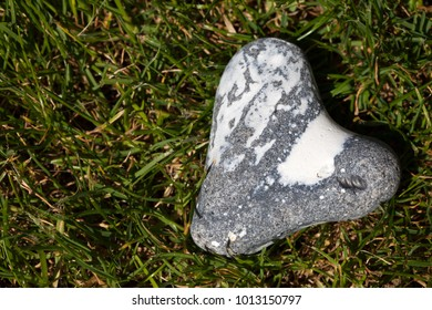 Heart shaped flintstone lying in the grass with copy space
