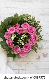 Heart shaped flower wreath with pink roses on white stone floor with butterflies