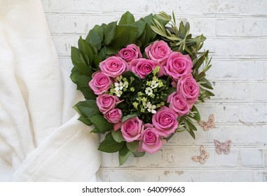 Heart shaped flower wreath with pink roses, rose leaves, white flowers, olive tree