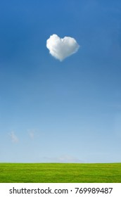 Heart shaped fluffy white cloud set in a bright blue sky with green grass countryside landscape below.