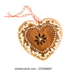 a heart shaped gingerbread christmas ornament isolated over a white background