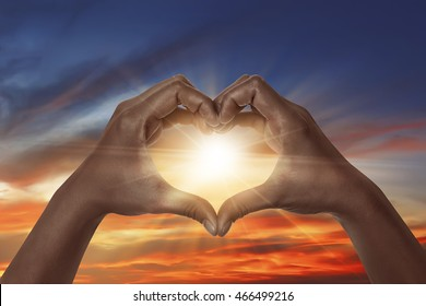 Heart shaped hand with sunrise background. heart shaped hand is a symbol of love, freedom, romance,