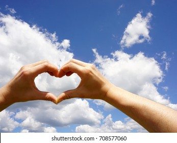 Heart shaped hands against summer sky