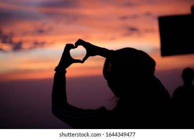Heart shaped hands with shadows and final light before the sun set.