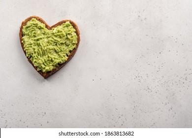 Herzgeformter gesunder Avocado Toast zum Valentinstag Frühstück