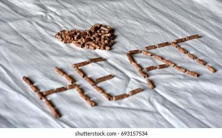 Heart shaped heating fuel wood pellet grains on white background