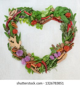 Heart shaped herb leaf and spice wreath with a selection of fresh herbs and spices with flowers on rustic white wood background with copy space.