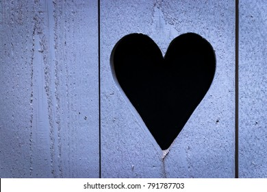 Heart shaped hole in wooden door/fence (blue tint).
