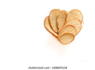 Heart shaped homemade wheat bread on white background. Sliced bread in shape of heart over white background.T op view. Copy space