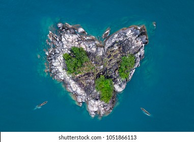 Heart shaped island, heart island in lake with canoe boats peddling to the shores. Aerial photo of heart isle in the ocean and lake Malawi kande beach