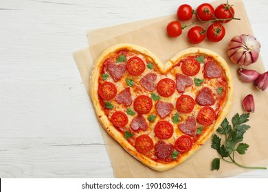 Heart shaped Italian pizza with salami,cherry tomatoes,garlics,parsley,pizza sauce,mozzella and olive oil on parchment paper with white wood table background.Love concept for Valentine's day   - Shutterstock ID 1901039461