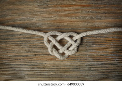 Heart shaped knot on wooden background