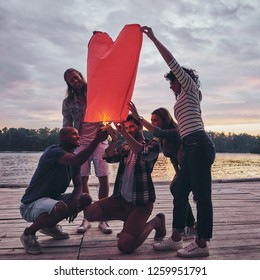 Heart shaped lantern. Full length of young people in casual wear lighting up sky lantern while standing on the pier