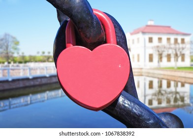 A heart shaped lock connected to chain, old house near the water defocused in the background.