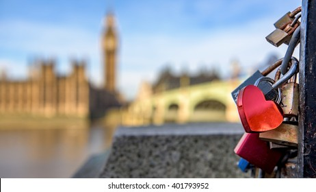 A heart shaped lock connected to other locks near Westminster bridge, Big Ben defocused in the background.