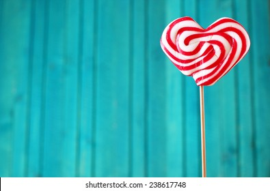 Heart shaped lollipop for Valentine's Day with turquoise copy space background