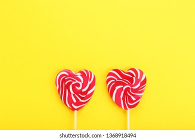 Heart shaped lollipops on yellow background