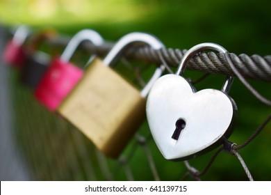 Heart shaped padlock on the bridge. Love locks hanging on wire mesh of footbridge over the river.