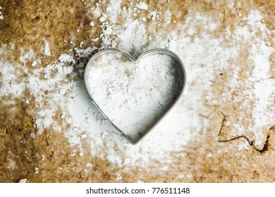 A heart shaped pastry cutter on a paste with icing sugar on it. The pastry cutter is used to make traditional christmas cookies - Alsace, France. The image could symbolize the love to bake.