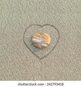 Heart shaped pebble on the sand beach