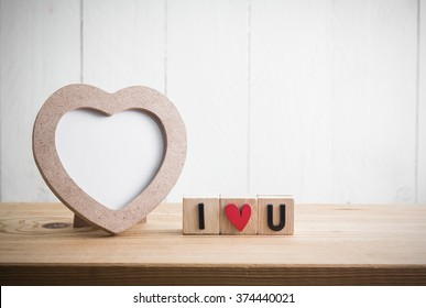 "Heart shaped photo frame with ""i love u"" in cube on wood table"