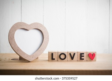 "Heart shaped photo frame with ""love"" in cube on wood table"