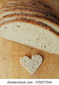 Heart shaped piece of bread in front of full bread