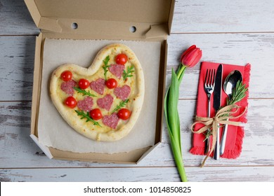 Heart shaped pizza in pizza box on wooden table with cutlery. Delivery pizza concept. Top view creative holiday background.