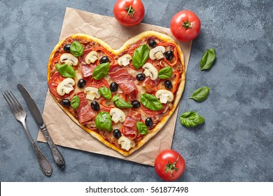 Heart shaped pizza love concept Valentine's Day flat lay romantic restaurant dinner Italian food. Olives, prosciutto, champignons, tomatoes and mozzarella meal on blue table background.