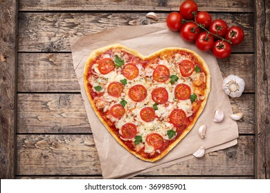 Heart shaped pizza margherita love food symbol with mozzarella, tomatoes, parsley, and garlic composition on cutting board, vintage wooden table background.