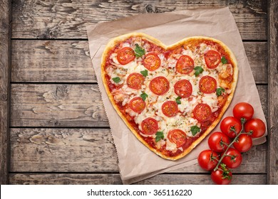 Heart shaped pizza margherita with tomatoes and mozzarella vegetarian meal on vintage wooden table background. Food concept of romantic love for Valentines Day.