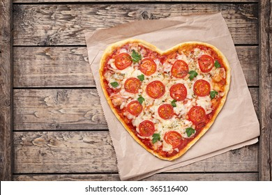 Heart shaped pizza margherita with tomatoes and mozzarella for Valentines Day on vintage wooden background. Food concept of romantic love.