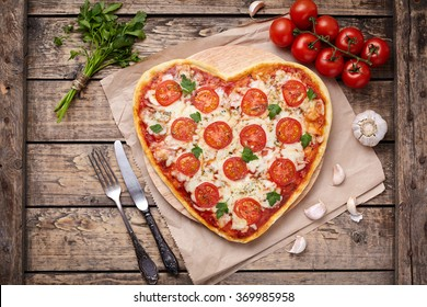 Heart shaped pizza margherita vegetarian love concept with mozzarella, tomatoes, parsley, knife, fork and garlic composition on cutting board, vintage wooden table background.