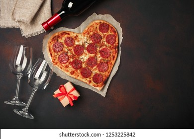 Heart shaped pizza with mozzarella, sausagered, wine bottle, two wineglass, gift box on rusty background. Top view.