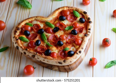 Heart shaped pizza on the wooden table background. Tasty pizza from oven with pepperoni, cherry tomatoes, olives and mozzarella , top view. Creative Valentines day background.