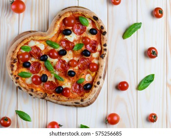 Heart shaped pizza on the wooden table background. Tasty pizza from oven with pepperoni, cherry tomatoes, olives and mozzarella , top view. Creative holidays background.