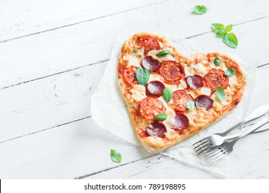 Heart shaped pizza over wooden background with copy space. Pizza with tomatoes, pepperoni, mozzarella cheese and basil for Valentine's day.