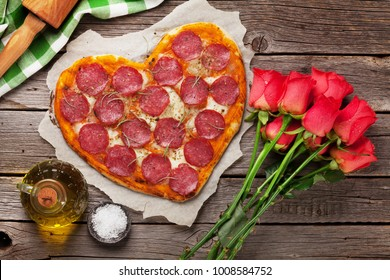 Heart shaped pizza with pepperoni and mozzarella and red rose flowers bouquet. Valentines day greeting card.