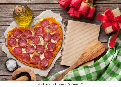 Heart shaped pizza with pepperoni and mozzarella. Valentines day greeting card. Top view with space for your text