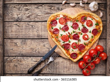 Heart shaped pizza with pepperoni, tomatoes and mozzarella on vintage wooden table background. Valentines day love concept.