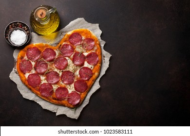 Heart shaped pizza with pepperoni. Valentines day greeting card. Top view with space for your text