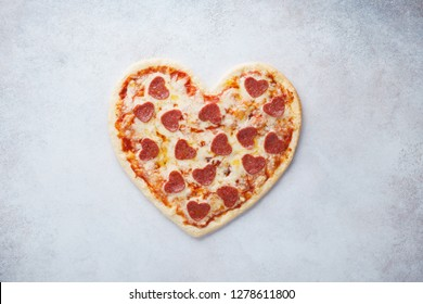 Heart shaped pizza with pepperoni. Valentines day romantic menu concept for restaurant or delivery.