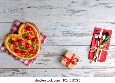 Heart shaped pizza with salami and mozzarella on old wooden background with gift and cutlery on red napkin. Top view creative Valentines day background.