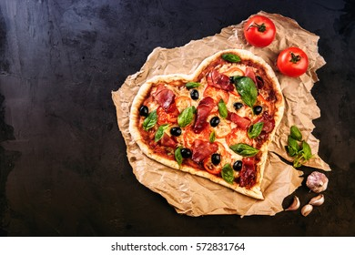 Heart shaped pizza with tomatoes and mozzarella for Valentines Day on vintage black background. Food concept of romantic love