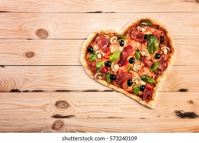 Heart shaped pizza with tomatoes and prosciutto for Valentines Day on vintage wooden background. Food concept of romantic love